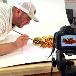 man adding finishing touches to sandwich for photoshoot