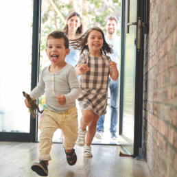 Smiling children entering a home.